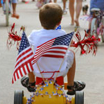 boy riding bicycle decorated with flags
