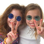 two girls wearing colored glasses and flashing peace signs