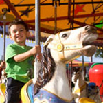 child riding carousel at amusement park