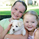 two girls holding a puppy