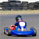 child driving a gocart around a racetrack