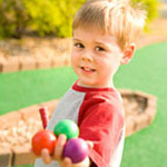 young boy holding golf balls at miniature golf course