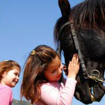 two girls petting a horse