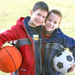 two boys holding sports balls