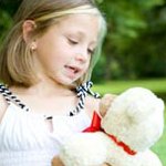 Little girl talking to her teddy bear
