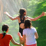 three girls playing in lawn sprinkler