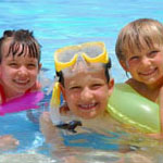 three children swimming in pool