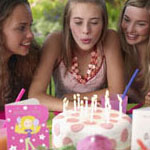 sixteen year old girl blowing out candles on birthday cake